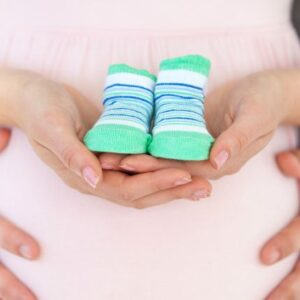 barriga de grávida segurando um sapato de bebê