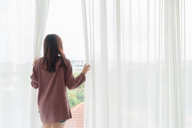 mulher na janela com a mão na cortina