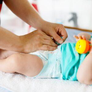 imagem de uma mão trocando a fralda do bebê